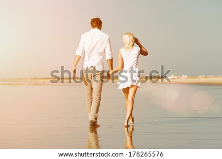 Couple on the beach in white clothing walking down, they might be on vacation or even honeymoon - stock photo