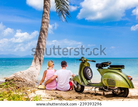 Couple on the beach with retro bike - stock photo