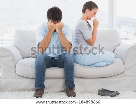 Couple on the couch after an argument at home in the living room - stock photo