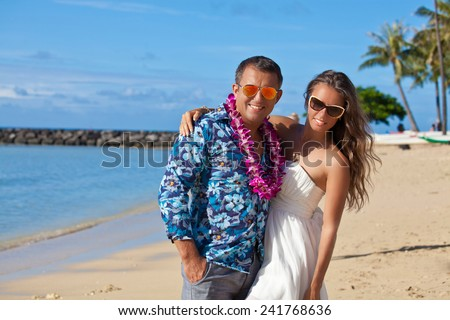 Couple on the Hawaiian beach. Young happy couple on beach smiling holding around each other. - stock photo