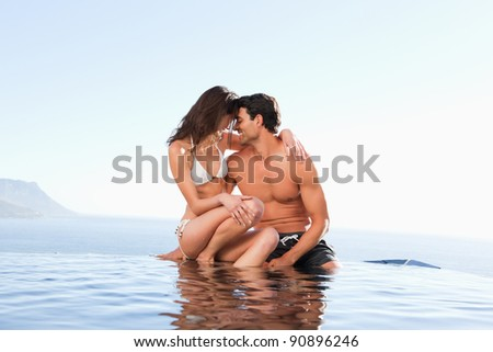 Couple on the pool edge together - stock photo