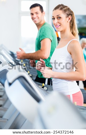 Couple on treadmill in fitness gym running for sport - stock photo