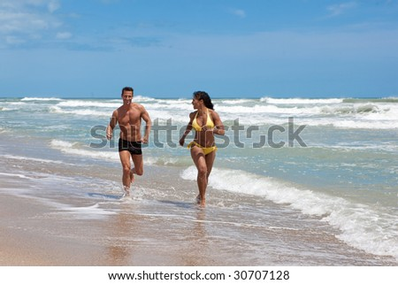 Couple on vacation running on a beach.  Both in swim suits.