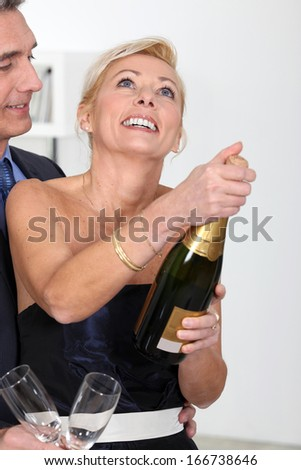 couple opening bottle of champagne - stock photo