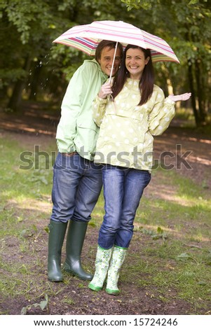 Couple outdoors in rain with umbrella smiling - stock photo