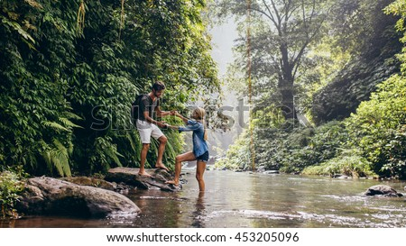 Couple outdoors on hike with man assisting woman across stream. Young couple in forest crossing the creek. - stock photo