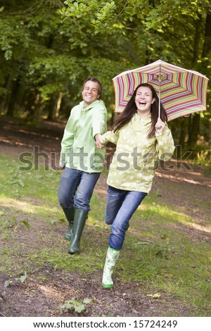 Couple outdoors running with umbrella smiling - stock photo