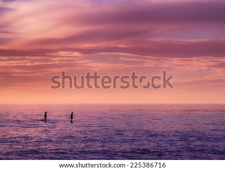 Couple paddle boarding at sunset - stock photo