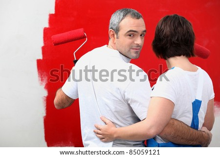 couple painting a wall - stock photo