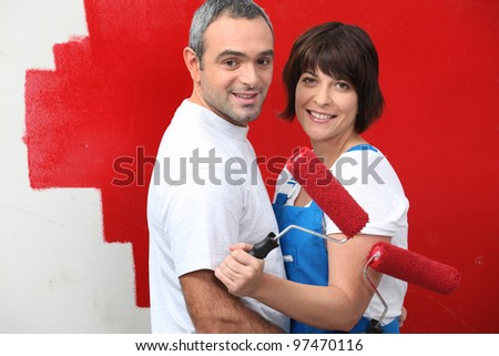 Couple painting a wall red - stock photo