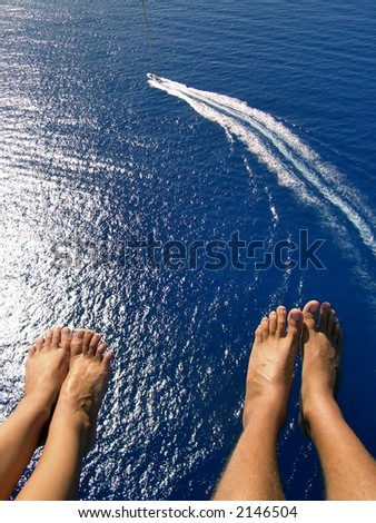 couple parasailing over beautiful blue ocean with view of boat - stock photo