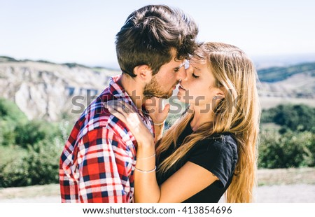 Couple passionated kiss. Young adults making trekking on the hills and sharing love emotions - stock photo