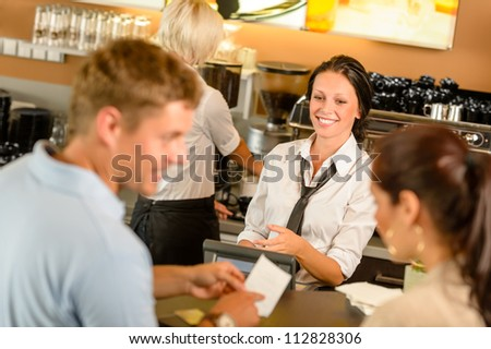 Couple paying bill at cafe cash desk smiling waitress bar - stock photo