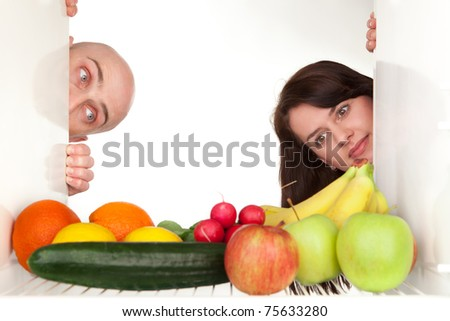Couple peeping around corner of refrigerator to look at healthy food and vegetables, White background and copy space. - stock photo
