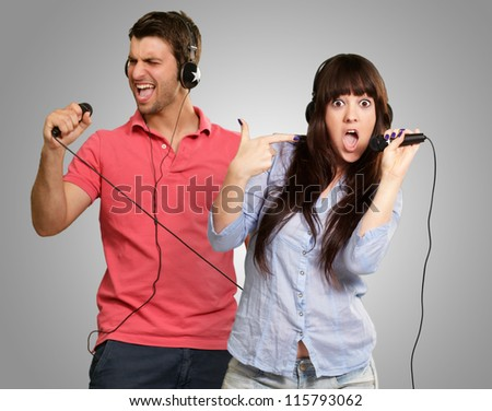 Couple Performing Song On Gray Background