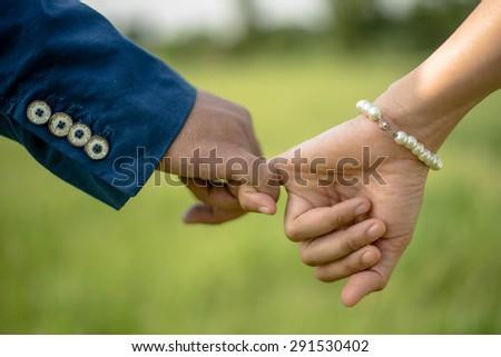 couple pinky swear on green grass field - stock photo