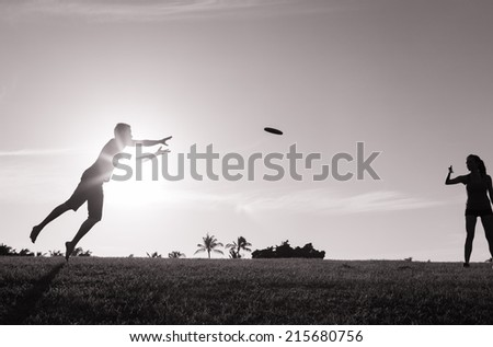 Couple play frisbee at the park - stock photo