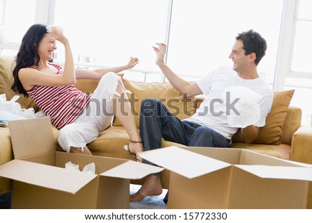 Couple playfully unpacking boxes in new home smiling - stock photo