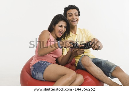 Couple playing a video game on a bean bag - stock photo