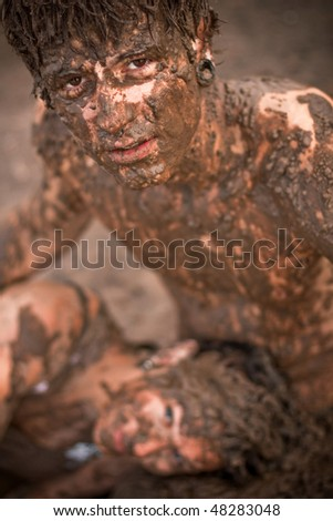 couple playing in the mud - stock photo