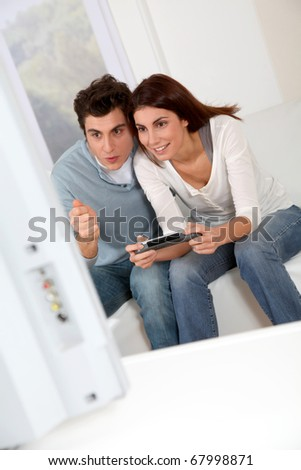 Couple playing video games at home - stock photo