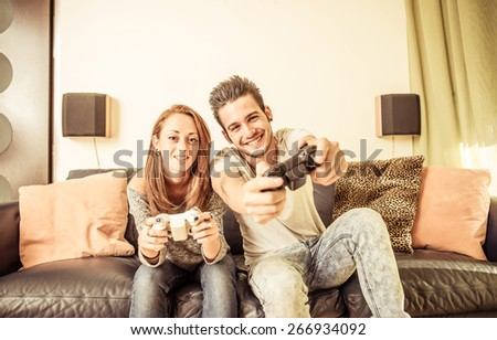 couple playing video games on the couch. concept about home entertainment, people and couple - stock photo