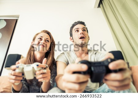 couple playing video games on the couch. concept about home entertainment, video games, people and couple - stock photo