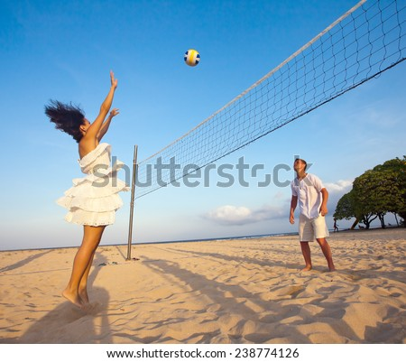 couple playing volleyball at the beach - stock photo