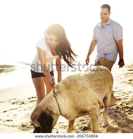 couple playing with pet dog. - stock photo