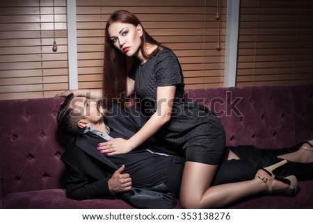 Couple playing. Woman sitting on man and looking into camera. Girl sitting on boy. Passion between lovers. Intimacy between boyfriend and girlfriend. - stock photo