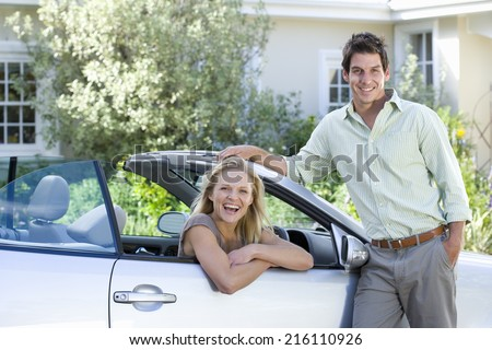 Couple posing by car - stock photo