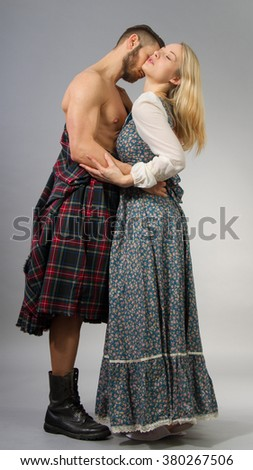 Couple posing in historical highland clothing. - stock photo