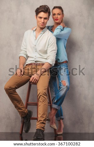 couple posing in studio background looking at the camera him sitting on a chair while she stands in the back resting her hands on his shoulders