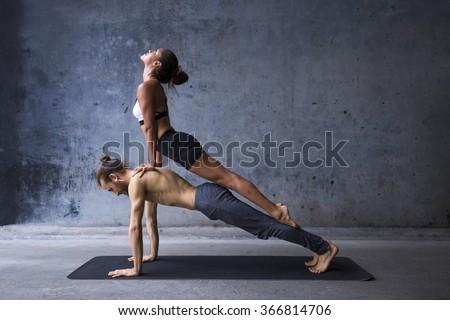 Couple practicing yoga together, upward facing dog on top of plank pose - stock photo