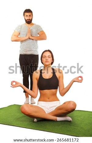 Couple practicing yoga, with focus on woman - stock photo