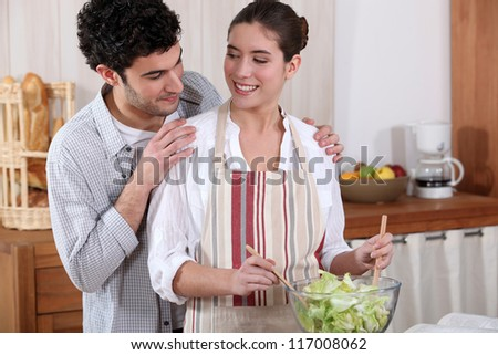 Couple preparing a salad together - stock photo