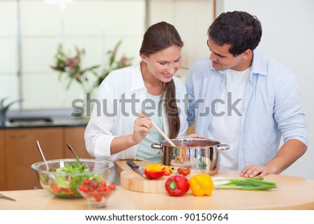 Couple preparing a sauce in their kitchen - stock photo