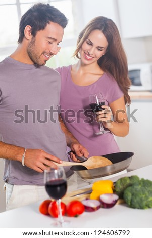 Couple preparing food and drinking in kitchen - stock photo