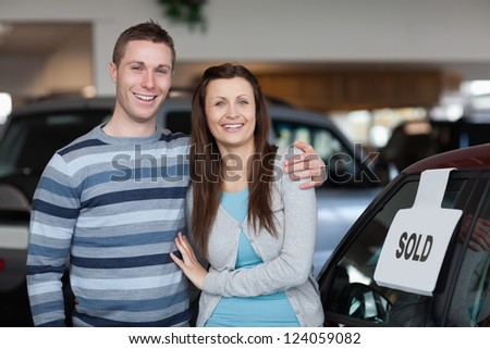 Couple purchasing a new car in a dealership - stock photo