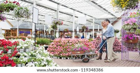 Couple pushing trolley in garden center - stock photo