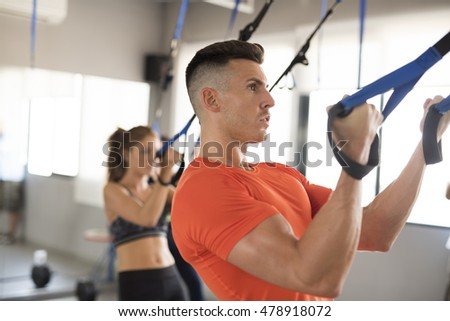 Couple raining with suspension rope in gym