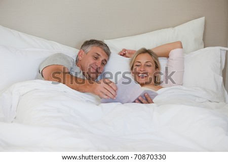 Couple reading a book in their bed at home - stock photo