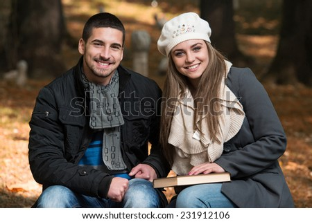 Couple Reading A Book - Relaxed Young Couple Reading Book In Park Bench - stock photo