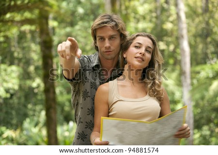 Couple reading a map in a tropical forest. - stock photo