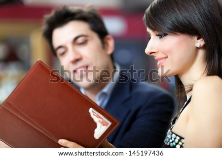 Couple reading a menu at the restaurant - stock photo