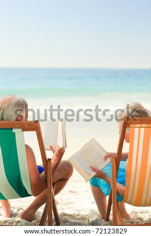 Couple reading at the beach - stock photo