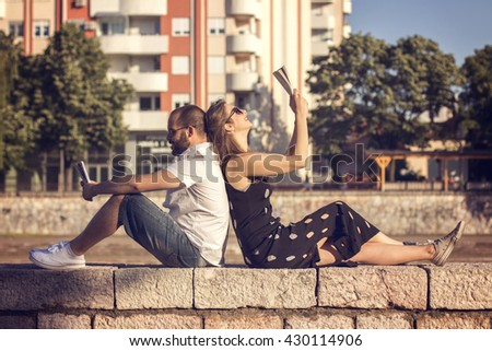 Couple reading books by the river on sunny day - stock photo