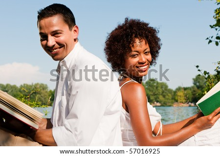 Couple reading books in the sunshine sitting at lake in summer - stock photo