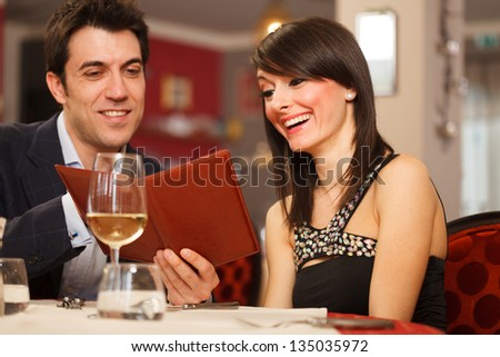 Couple reading the menu in a restaurant - stock photo
