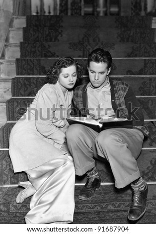 Couple reading together on stairs - stock photo